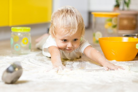 Little boy child laying on very messy kitchen floor. Toddler covered in white baking flour. Stock Photo