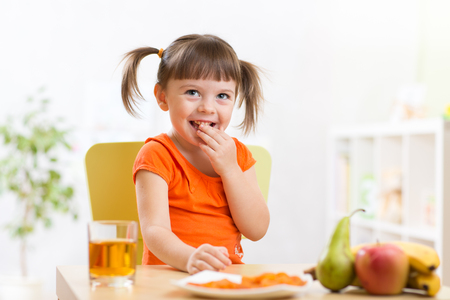 Smiling child girl sitting on the table with fruits and juice in nursery