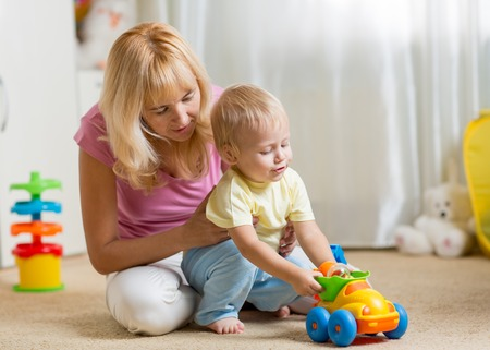 baby boy: Mother and child son playing with toy car on nursery floor
