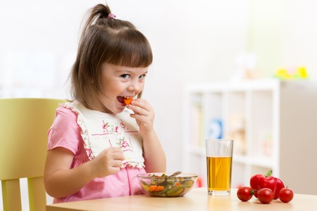 feed: Cute child little girl eating healthy vegetables at home