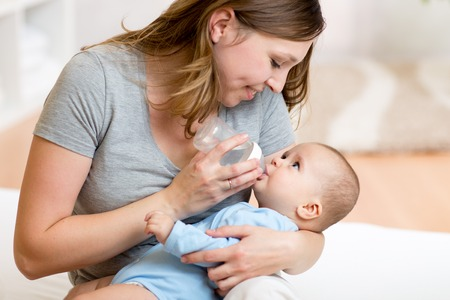 cute mother feeding her adorable baby at home Stock Photo - 48132630