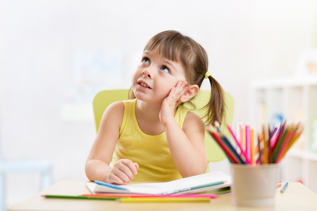 thoughful child girl drawing with colorful pencils in nursery room