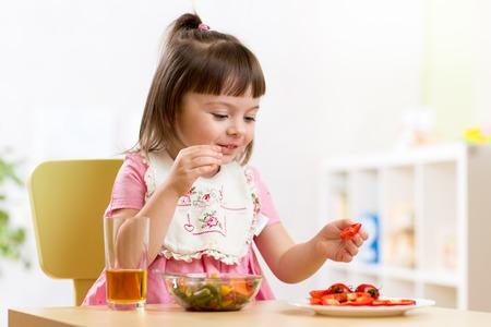 kinder: ni�o comiendo alimentos saludables en la guarder�a o en casa Foto de archivo