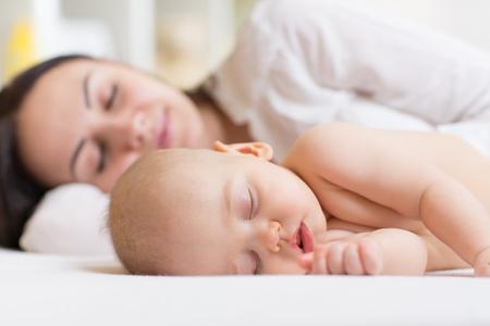 kisbabák: Csecsemő, fiú és az anyja pihentető egy fehér hálószobában Stock fotó