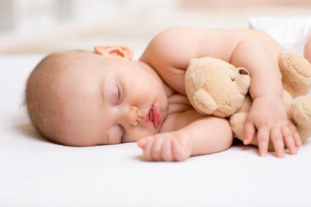 Zorgeloze slaap baby jongen met zacht speelgoed op bed