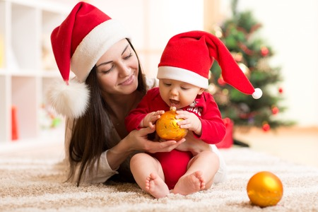 mom baby: Portrait of happy mother and adorable baby holding bauble against domestic festive backdrop with Christmas tree