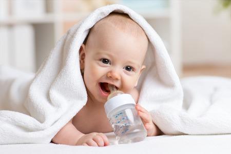 Happy baby boy drinks water from bottle wrapped towel after bath Foto de archivo