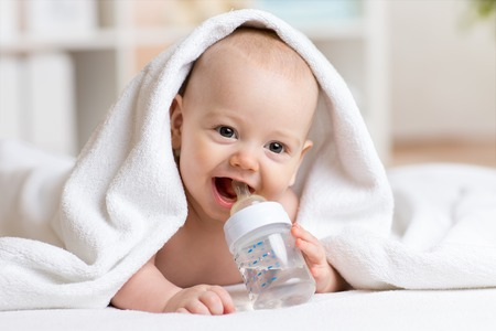 Happy baby boy drinks water from bottle wrapped towel after bath Standard-Bild