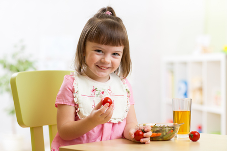 preschooler: happy child girl eats dinner and shows tomatoes Stock Photo