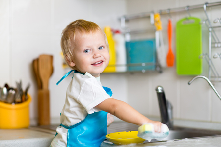 Adorable toddler child washing dishes in kitchen. Little boy having fun with helping to his mother with housework. Stock Photo