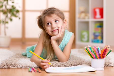 escuela primaria: niño de la muchacha soñadora dibuja con lápices de colores situada en el piso en el hogar Foto de archivo