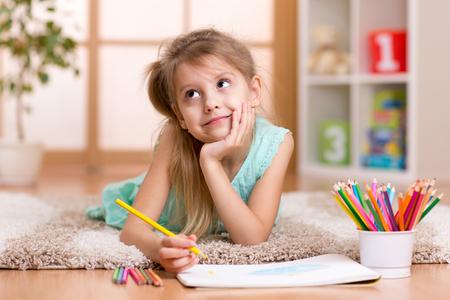 bambini pensierosi: sognante ragazza bambino disegna con matite colorate sdraiato sul pavimento a casa