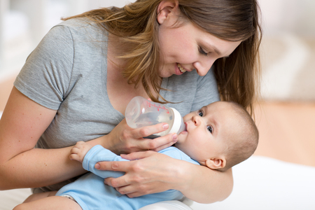 Mère donne à boire bébé de l'eau de la bouteille Banque d'images