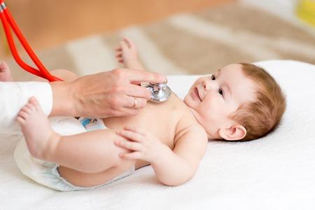 chory: Pediatra bada trzy miesiące baby boy. Lekarz za pomocą stetoskop słuchać piersiowej sprawdzanie pulsu dla dzieci. Uśmiechnięte dziecko patrząc na lekarza.