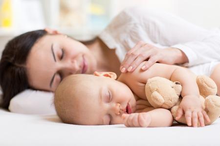 baby s: mooie vrouw en haar zoon kleine baby slapen samen in een slaapkamer