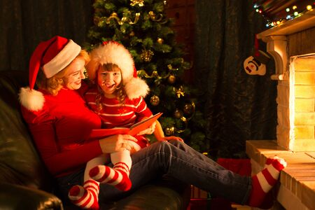 story: Christmas story time with mother and child daughter in front of fireplace at x-mas tree
