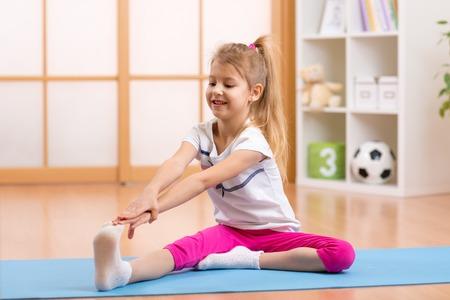 陽気な子供女の子自宅体操を行う