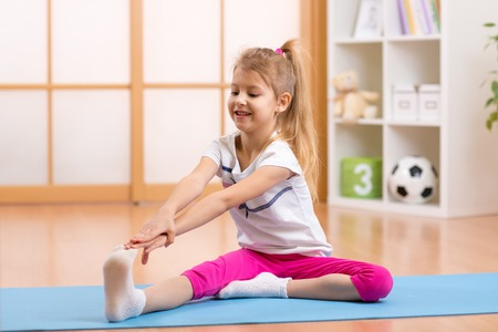 gymnastique: Sportive enfant fille faisant gymnastique à la maison