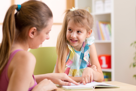 elementary: Mother or teacher woman helping child girl with homework