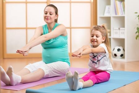 gymnastics: Schwangere Frau mit ihrem ersten Kind Tochter Turnen im Wohnzimmer
