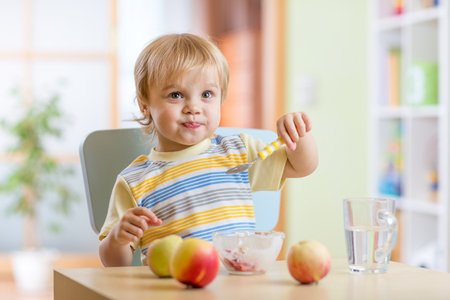 Beautiful child boy eating healthy food with a spoon at home