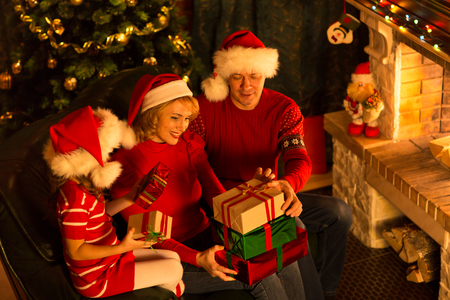 three persons: Christmas family of three persons in red hats with gift boxes Stock Photo