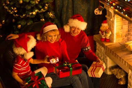three persons: Happy family of three persons in Santa hats with gifts sitting at Christmas tree near fireplace
