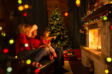 Happy family sitting by fireplace at Christmas tree.  Child shows on fire. Stock Photo