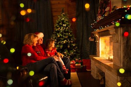 Gelukkig gezin - vader, moeder en hun dochter door een open haard op Kerstmis