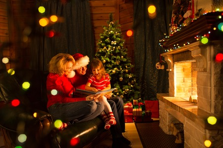 warm home: Father, mother and their daughter reading a book by a Christmas tree in cozy living room in winter