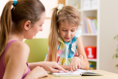 Mother or teacher helping child daughter to reading Stock Photo