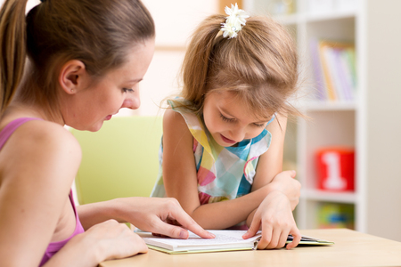 reading a book: Mother teaching her child daughter to read Stock Photo