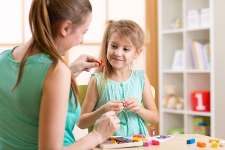 kids toys: child kid girl and mother play colorful clay toys at nursery at home Stock Photo