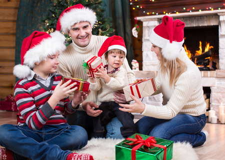 fireplace family: Family exchanging gifts in front of Christmas tree and fireplace Stock Photo