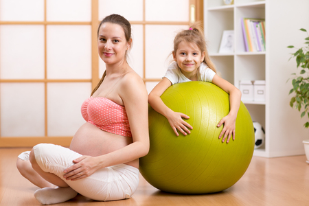 fitball: Family, children, pregnancy, fitness, healthy lifestyle concept - happy pregnant woman exercising with fitball at home