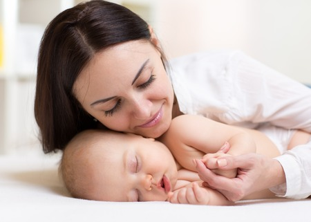 newborn baby boy: happy beautiful mother looking at sleeping baby little son