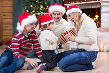 fireplace family: Happy family in Santa hats giving gift to youngest child sitting at Christmas tree near fireplace Stock Photo