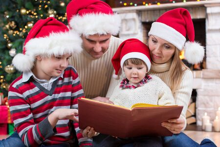 Family reading Christmas book together in front of fire place