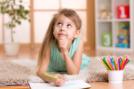 nursery school: dreamy kid girl draws with color pencils lying on floor at home Stock Photo