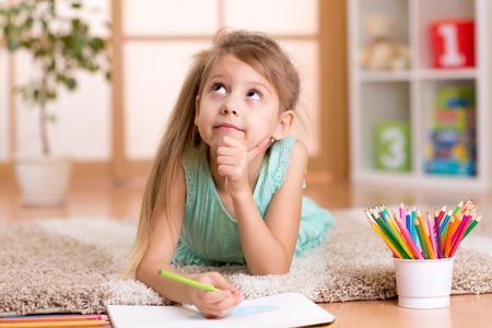 bambini pensierosi: sognante bambino ragazza disegna con matite colorate sdraiato sul pavimento a casa