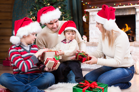 fireplace family: Happy family in Santa hats with gifts sitting at Christmas tree near fireplace