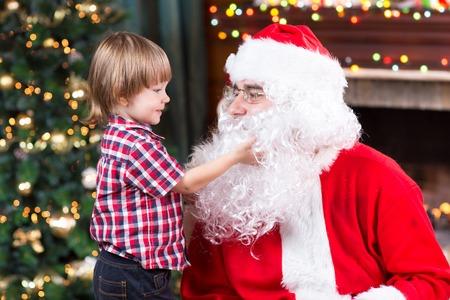 fake christmas tree: Surprised child boy looks at fake Santa Claus with fake beard sitting opposite Christmas tree Stock Photo