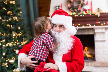 hat of santa claus: Santa Claus and little child boy. Kid telling his Christmas wishes in Santa Claus near the Christmas tree opposite fireplace Stock Photo