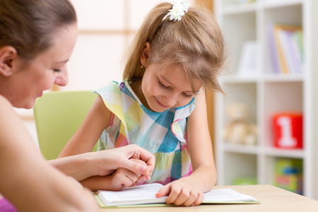 Preschooler Child Girl Reading with Mother In Nursery at Home
