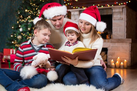 fireplace family: Family reading a book together near Christmas tree in front of fireplace Stock Photo