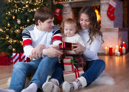 fireplace family: Happy family with little son sitting near Christmas tree and fireplace.