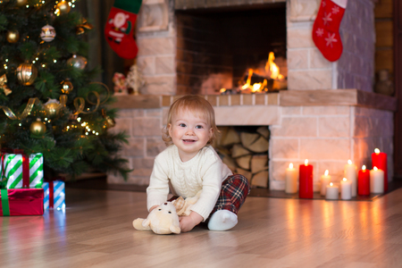 fire place: Kid boy playing with toy gift on Christmas eve at fireplace. Decorated living room with traditional fire place.