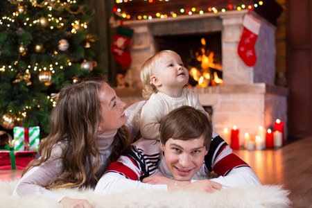 fireplace family: Happy family with little son lying near Christmas tree and fireplace  in living room