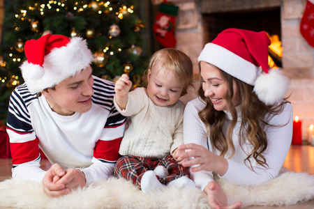 fireplace living room: Happy family with child son lying near Christmas tree and fireplace  in living room Stock Photo
