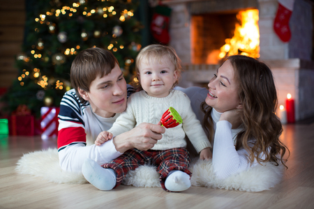 fireplace family: Happy family with little son playing near Christmas tree and fireplace  in living room